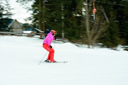 A beautiful woman in red gear learns to ride skiing in the Ukrainian Carpathians