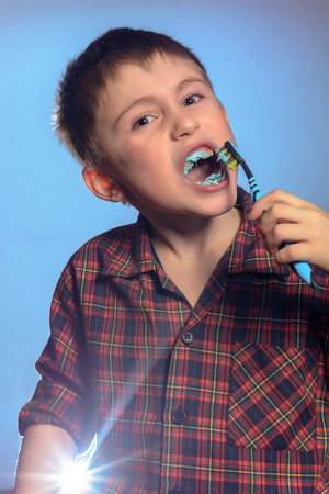 A cute boy in a pajamas brushes teeth with toothpaste before bedtime on a blue background 2019 Reklamní fotografie