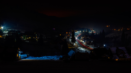 A wonderful panorama of the night mountain village of Ukraine with car tracks