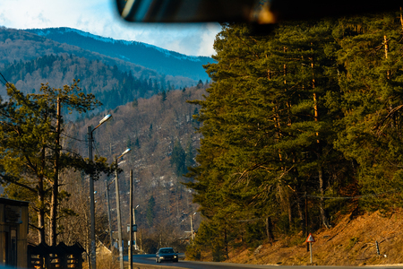 View from the first person from the car interior to the serpentine highway in the mountainous area