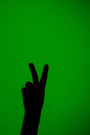 The soft hand showing the victory sign is isolated on a red background 2019 Stock Photo