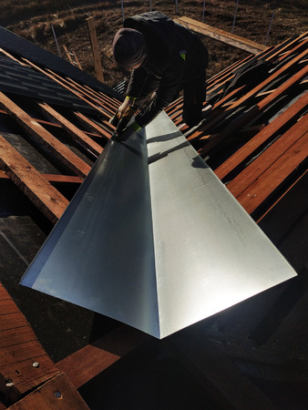 The master performs the installation of a metallic sheet at the refraction point of the roof to drain water during rain 2019