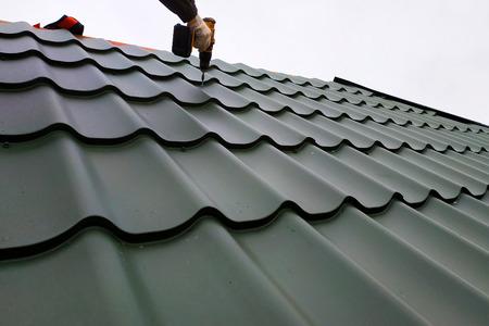 El trabajador profesional trabaja en la instalación del techo del techo con las hojas de la teja metálica y taladra el tornillo con el taladro 2019