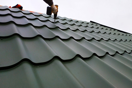 The professional worker works on installation of a roof of a roof by sheets of a metal tile and drills a screw with a drill 2019 Zdjęcie Seryjne - 119238424
