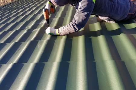 The professional worker works on installation of a roof of a roof by sheets of a metal tile and drills a screw with a drill 2019