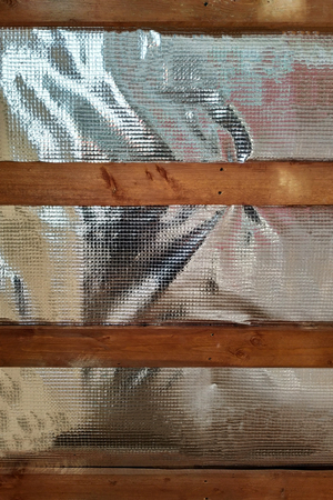 Insulation of the roof of the house on the inside with the use of a wrapper film and fixing boards
