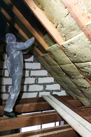A man in a protective overalls puts mineral wool between the beam of the roof of the house for his warming from the cold