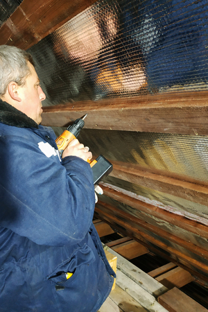 The carpenter uses a cordless drill and screw the screws into boards that hold foil film and mineral wool to heal the roof of the house Imagens