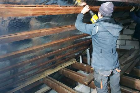 The carpenter uses a cordless drill and screw the screws into boards that hold foil film and mineral wool to heal the roof of the house Banco de Imagens