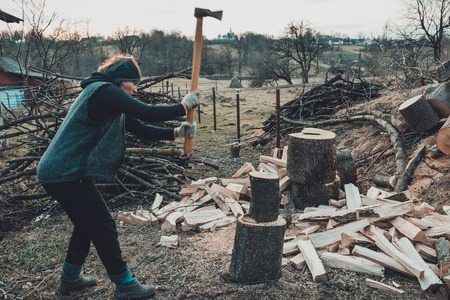 A rural woman shoots an ash tree wood for harvesting for the winter with an ax 2019