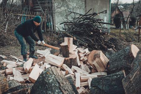 Ein starker Mann erntet im Hinterhof des Hauses Brennholz für den Winter und schneidet den großen und robusten Grasbaum 2019 Standard-Bild