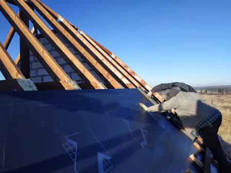 The worker stapler attaches to the rafter gidrobarier on the background can see the sky
