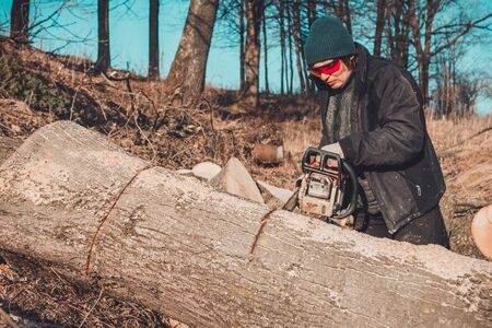 Young rural girl cut a tree chainsaw in gloves, cook firewood for winter
