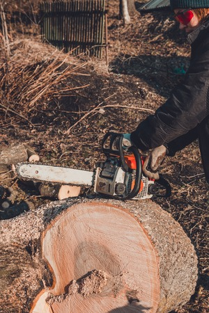 A young woman launches a chainsaw for cutting wood in the countryside
