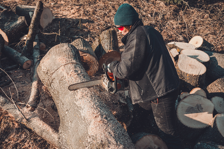 Young rural girl cut a tree chainsaw in gloves, cook firewood for winter 2019