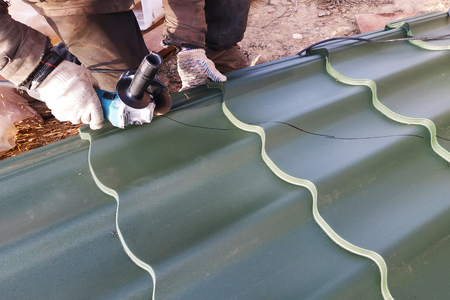 The master cuts a professional metal sheet for installation on the roof of the house 免版税图像 - 127010145