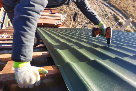 The professional worker works on installation of a roof of a roof by sheets of a metal tile and drills a screw with a drill Stock Photo