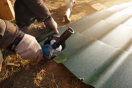 The master cuts a professional metal sheet for installation on the roof of the house 2019