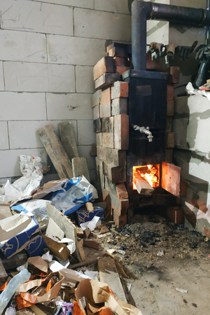 The wood-burning stove burns with open doors in violation of the safety and poses a threat to the building through the potential fire resulting in a fire Stock Photo