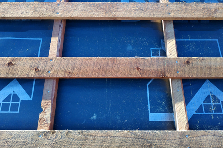 Preparation of roof roof before installation of sheets of metal tiles with insulation, waterproofing with the help of film, boards and bars Stock Photo