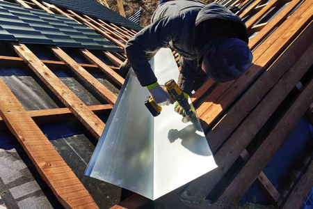 The master performs the installation of a metallic sheet at the refraction point of the roof to drain water during rain