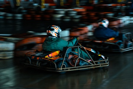 Dynamic karting competition at speed with blurry motion on an equipped racecourse 2019 Фото со стока