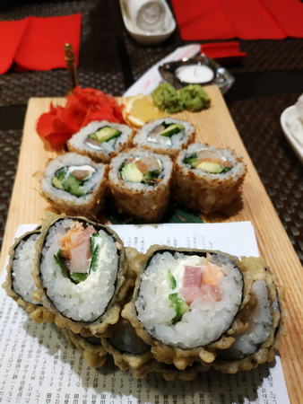 Hot sushi are served on a wooden board with marinated ginger and isabi. 2019 Standard-Bild