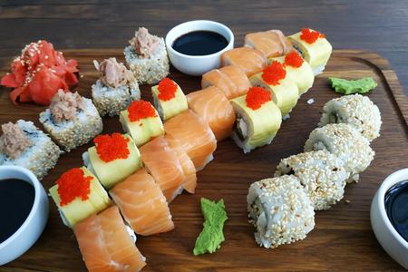 Sushi rolls set served on black stone slate on dark background 2019.