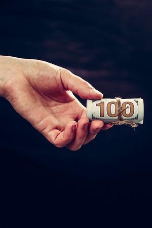 La mano di una donna che tiene 100 banconote da cento, un trasferimento di denaro, uno sfondo scuro. 2019 Archivio Fotografico