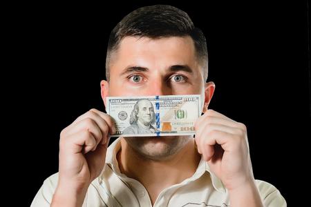 uomo d'affari in un vestito con una bocca chiusa di banconote da cento dollari, silenzioso per soldi. il concetto di corruzione e concussione. 2019