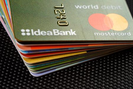 Lviv, Ukraine - 26 April 2019 : Stack of colorful credit cards of the Ukrainian bank titled IdeaBank 2020