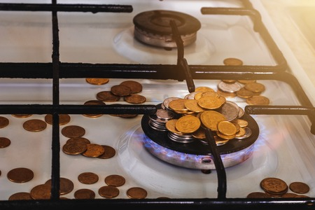 Coins are scattered and laid out on a pyramid on a gas stove, gas is lit.