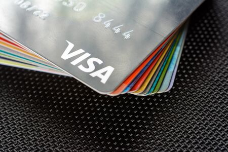 Lviv, Ukraine - 26 April 2019 : Close-up of Visa credit cards placed on a dark background Редакционное