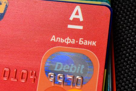 Lviv, Ukraine - 26 April 2019 : Stack of colorful credit cards of the Ukrainian bank titled AlfaBank Редакционное