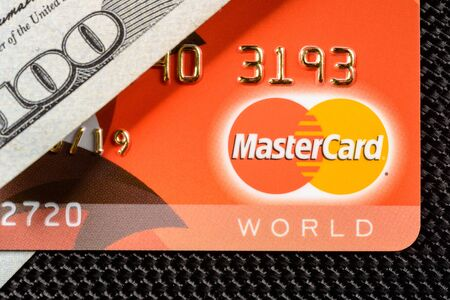 Lviv, Ukraine - 26 April 2019 : A red card with a MasterCard logo is placed on a one hundred dollar banner close-up.