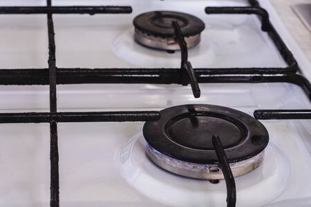On the white gas stove the burner is lit from which the flame of natural gas is visible. 2019 Imagens