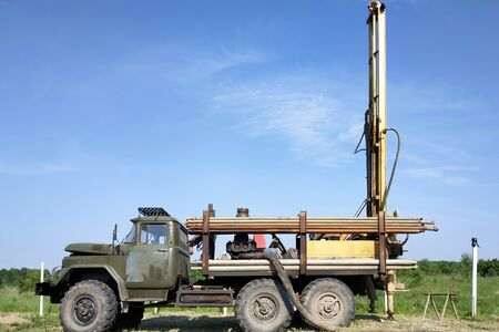 At the time there is a large car that drills a well to the water. 2019 Stock Photo