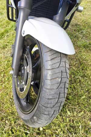 Sports motorcycle wheel close-up on grass background. 2019