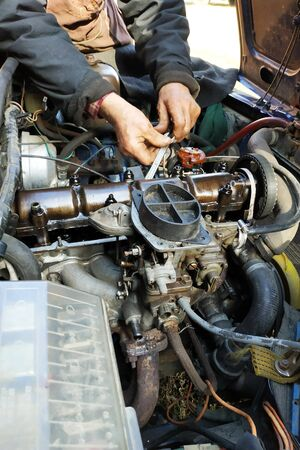 The master in the garage taps the valves in the old car, VAZ car, an old worn-out car. 2019 Stock Photo