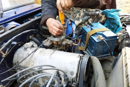 The auto locksmith tightens the valves of the VAZ brand in the garage. 2019