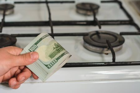 The man holds a bill of lading in his hands in a sign of the rise in price of natural gas near the gas stove. 2019 Stock Photo