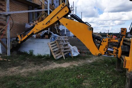 The excavator digs a dart around a building that is under construction. 2019