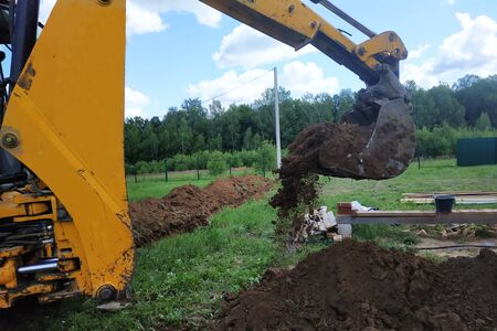 In a private plot, the excavator digs a trench. 2019