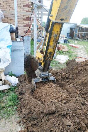 The excavator digs a small trench in the yard. 2019 Stock Photo