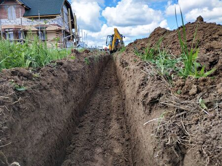 Construction excavator digging a shallow groove for electrical wiring or cable. 2019