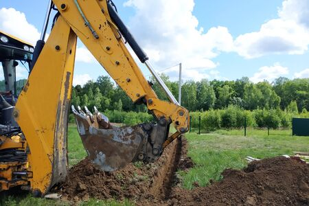 A yellow excavator digging a trench on the construction site, a close-up, against the sky. 2019 Stock Photo
