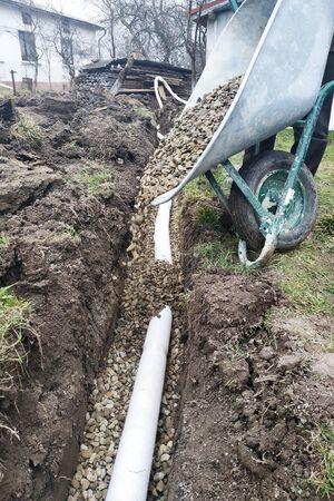 Nel cortile, i lavoratori eseguono lavori di drenaggio per lo scarico dell'acqua. 2019