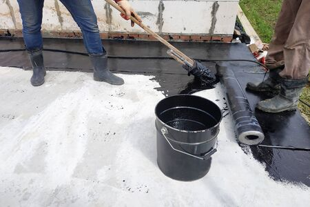 Masters perform work on the waterproofing of concrete in the open air. 2019