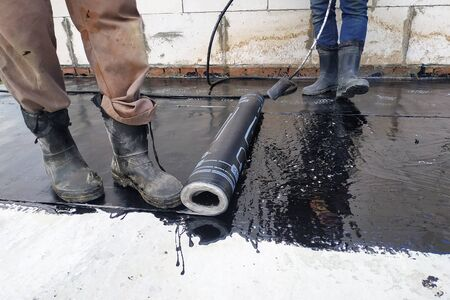 Worker covered surface, bitumen primer for improving adhesion during surfacing, rolled waterproofing, during the installation of isolation on industrial or household objects. 2019