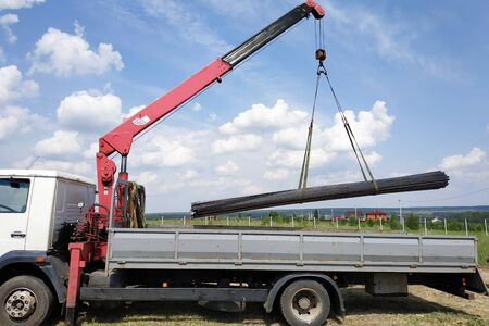 The truck crane in the field on the private land unloads the metal profile. 2019